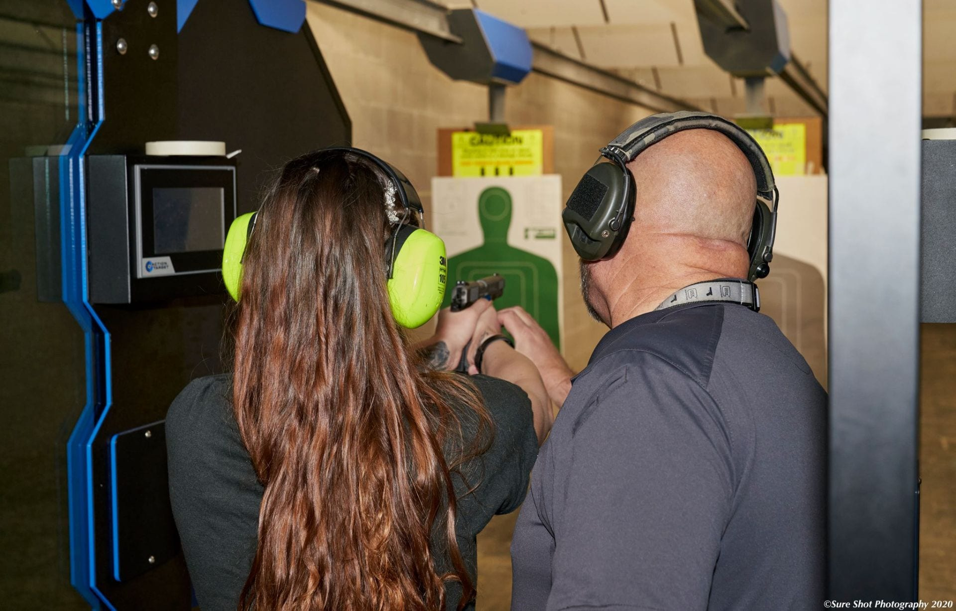 A woman learning to shoot after booking a course