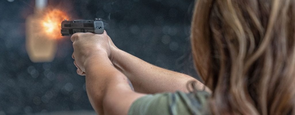 a woman shooting a handgun - join our newsletter