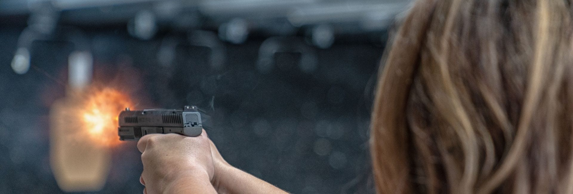 a woman shooting a handgun - join our newsletter